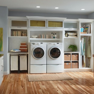 Photo of a large traditional l-shaped utility room in Other with glass-front cabinets, white cabinets, a side by side washer and dryer, medium hardwood flooring and grey walls.