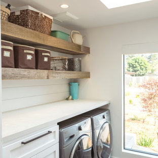 Large rural utility room in Other with white cabinets, white walls, a side by side washer and dryer and white worktops.