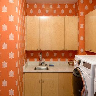Foto di una sala lavanderia minimal di medie dimensioni con lavello sottopiano, ante lisce, ante in legno chiaro, top in quarzite, pareti arancioni, pavimento in ardesia, lavatrice e asciugatrice affiancate e pavimento beige