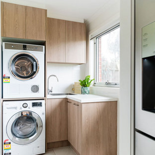 Inspiration for a small modern l-shaped dedicated laundry room in Melbourne with flat-panel cabinets, quartz benchtops, blue splashback, ceramic splashback, porcelain floors, beige floor, white benchtop, a drop-in sink, light wood cabinets, white walls and a stacked washer and dryer.