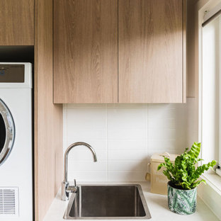 Design ideas for a small modern l-shaped dedicated laundry room in Melbourne with flat-panel cabinets, quartz benchtops, porcelain floors, beige floor, white benchtop, a drop-in sink, light wood cabinets, white splashback, porcelain splashback, white walls and a stacked washer and dryer.