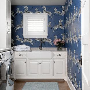 Klassisk inredning av en grå l-formad grått tvättstuga enbart för tvätt, med en rustik diskho, luckor med upphöjd panel, vita skåp, flerfärgad stänkskydd, flerfärgade väggar, mellanmörkt trägolv, en tvättmaskin och torktumlare bredvid varandra och brunt golv