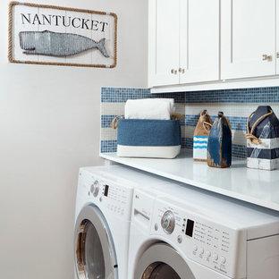 Bild på en liten maritim vita linjär vitt tvättstuga enbart för tvätt, med skåp i shakerstil, vita skåp, träbänkskiva, vita väggar, klinkergolv i porslin och en tvättmaskin och torktumlare bredvid varandra