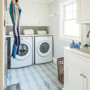 Idee per una sala lavanderia costiera con lavello da incasso, ante con riquadro incassato, ante bianche, pareti grigie, lavatrice e asciugatrice affiancate, pavimento blu e top bianco
