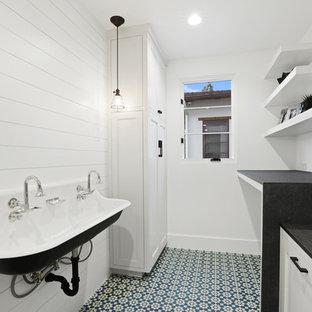 Idee per una piccola sala lavanderia minimalista con lavatoio, pareti bianche, pavimento in cemento, lavatrice e asciugatrice affiancate, pavimento blu, ante con riquadro incassato e ante bianche