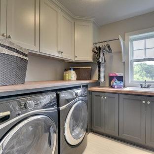Foto på en stor vintage l-formad tvättstuga enbart för tvätt, med en nedsänkt diskho, luckor med infälld panel, grå skåp, laminatbänkskiva, grå väggar, klinkergolv i keramik och en tvättmaskin och torktumlare bredvid varandra