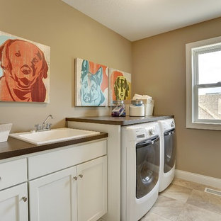Example of a large transitional galley porcelain tile laundry room design in Minneapolis with a drop-in sink, recessed-panel cabinets, white cabinets, laminate countertops, brown walls and a side-by-side washer/dryer