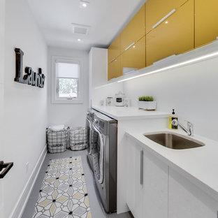 トロントのコンテンポラリースタイルのおしゃれなランドリールーム (アンダーカウンターシンク、フラットパネル扉のキャビネット、黄色いキャビネット、白い壁、左右配置の洗濯機・乾燥機、白いキッチンカウンター) の写真