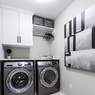 Esempio di una piccola sala lavanderia design con ante lisce, ante bianche, top in laminato, pareti grigie, pavimento in gres porcellanato e lavatrice e asciugatrice affiancate
