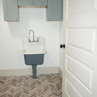Foto di una sala lavanderia country di medie dimensioni con ante lisce, ante grigie, pareti bianche, pavimento in mattoni, lavatrice e asciugatrice affiancate, pavimento marrone e lavello integrato