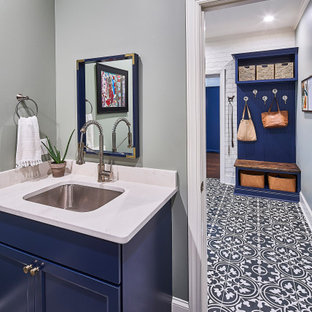 Inspiration for a mid-sized transitional galley utility room in Charlotte with an undermount sink, recessed-panel cabinets, blue cabinets, quartz benchtops, white splashback, grey walls, ceramic floors, a stacked washer and dryer, multi-coloured floor and white benchtop.