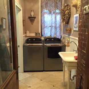 Esempio di una sala lavanderia vittoriana di medie dimensioni con lavello stile country, pareti beige, pavimento in travertino e lavatrice e asciugatrice affiancate
