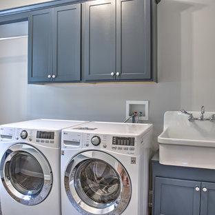 Immagine di una sala lavanderia american style di medie dimensioni con lavello stile country, ante con riquadro incassato, ante grigie, top in quarzite e lavatrice e asciugatrice affiancate