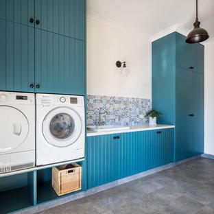 Foto di una lavanderia country con lavello da incasso, ante a persiana, ante verdi, top in quarzo composito, pareti multicolore, lavatrice e asciugatrice affiancate e top grigio