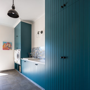Inspiration for a country laundry room in Perth with louvered cabinets, green cabinets, quartz benchtops, a side-by-side washer and dryer and grey benchtop.