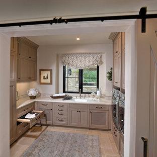 Idee per un'ampia sala lavanderia mediterranea con lavello sottopiano, ante con riquadro incassato, ante beige, top in quarzite, pareti bianche, pavimento in pietra calcarea, lavatrice e asciugatrice affiancate e pavimento beige