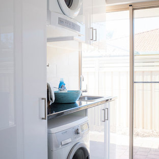 This is an example of a small modern single-wall separated utility room in Perth with a single-bowl sink, flat-panel cabinets, white cabinets, beige walls, ceramic flooring, a stacked washer and dryer, grey floors and black worktops.