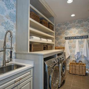 Ispirazione per una sala lavanderia costiera di medie dimensioni con lavello da incasso, ante con bugna sagomata, top in legno, pavimento con piastrelle in ceramica, lavatrice e asciugatrice affiancate e ante grigie
