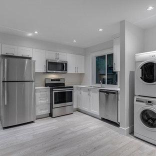 Exempel på en mycket stor modern vita l-formad vitt tvättstuga enbart för tvätt, med en undermonterad diskho, skåp i shakerstil, vita skåp, bänkskiva i kvarts, vita väggar, ljust trägolv, en tvättpelare och grått golv