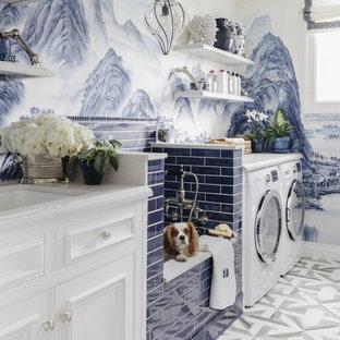 Modelo de lavadero multiusos, clásico, con armarios con rebordes decorativos, puertas de armario blancas, paredes multicolor, lavadora y secadora juntas y suelo multicolor