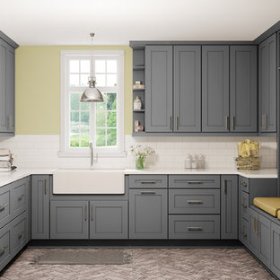 Inspiration for a large modern u-shaped dedicated laundry room with a farmhouse sink, shaker cabinets, grey cabinets, marble benchtops, yellow walls, porcelain floors, a stacked washer and dryer, beige floor and white benchtop.
