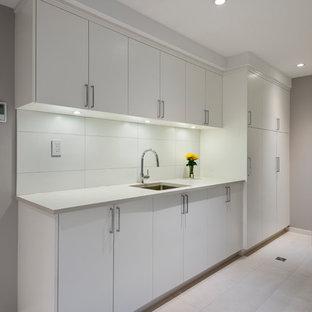 Aménagement d'une buanderie parallèle asiatique multi-usage et de taille moyenne avec un évier encastré, un placard à porte plane, des portes de placard blanches, un plan de travail en quartz modifié, un mur gris, un sol gris et un plan de travail noir.