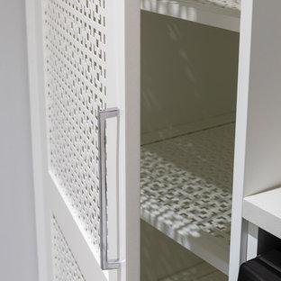 Idée de décoration pour une buanderie parallèle asiatique multi-usage et de taille moyenne avec un évier encastré, un placard avec porte à panneau encastré, des portes de placard blanches, un plan de travail en quartz modifié, un mur blanc, un sol en carrelage de céramique, un sol blanc et un plan de travail blanc.