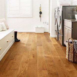 Lantlig inredning av en stor grå linjär grått tvättstuga enbart för tvätt, med luckor med infälld panel, skåp i mörkt trä, bänkskiva i kvarts, vita väggar, ljust trägolv, en tvättmaskin och torktumlare bredvid varandra och brunt golv