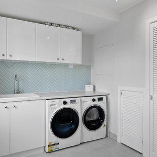 Ispirazione per una lavanderia costiera con lavello da incasso, ante lisce, ante bianche, paraspruzzi blu, pareti bianche, lavatrice e asciugatrice affiancate, pavimento grigio e top grigio