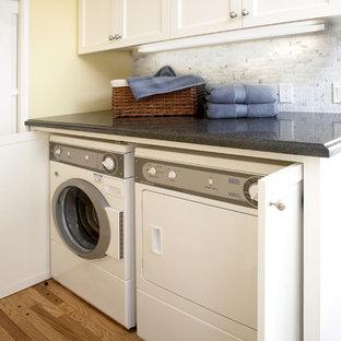 Idéer för mellanstora vintage grått tvättstugor, med skåp i shakerstil, vita skåp, granitbänkskiva, gula väggar, mellanmörkt trägolv, en tvättmaskin och torktumlare bredvid varandra och brunt golv