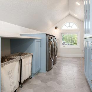 Idéer för att renovera en lantlig vita parallell vitt tvättstuga enbart för tvätt, med en undermonterad diskho, skåp i shakerstil, blå skåp, bänkskiva i kvarts, vitt stänkskydd, stänkskydd i keramik, vita väggar, klinkergolv i porslin, en tvättmaskin och torktumlare bredvid varandra och grått golv
