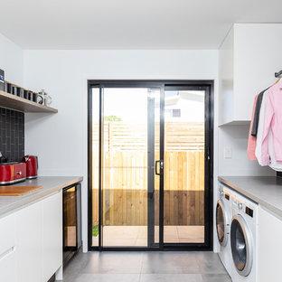 Exempel på ett mellanstort modernt grå parallellt grått grovkök, med en enkel diskho, släta luckor, vita skåp, granitbänkskiva, svarta väggar, klinkergolv i keramik, en tvättmaskin och torktumlare bredvid varandra och grått golv