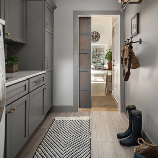 Photo of a mid-sized transitional single-wall utility room in Chicago with an undermount sink, shaker cabinets, grey cabinets, quartz benchtops, multi-coloured splashback, cement tile splashback, grey walls, porcelain floors, a side-by-side washer and dryer, grey floor and white benchtop.