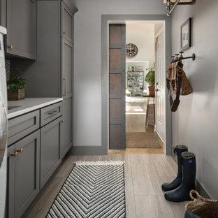Klassisk inredning av ett mellanstort vit linjärt vitt grovkök, med en undermonterad diskho, skåp i shakerstil, grå skåp, bänkskiva i kvarts, flerfärgad stänkskydd, stänkskydd i cementkakel, grå väggar, klinkergolv i porslin, en tvättmaskin och torktumlare bredvid varandra och grått golv