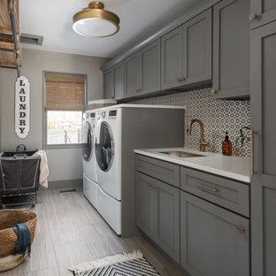 Exempel på en mellanstor klassisk vita linjär vitt tvättstuga enbart för tvätt, med en undermonterad diskho, skåp i shakerstil, grå skåp, bänkskiva i kvarts, flerfärgad stänkskydd, stänkskydd i cementkakel, grå väggar, klinkergolv i porslin, en tvättmaskin och torktumlare bredvid varandra och grått golv