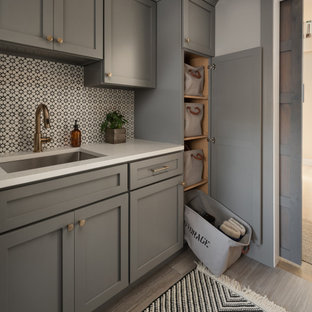 Design ideas for a mid-sized transitional single-wall utility room in Chicago with an undermount sink, shaker cabinets, grey cabinets, quartz benchtops, multi-coloured splashback, cement tile splashback, grey walls, porcelain floors, a side-by-side washer and dryer, grey floor and white benchtop.