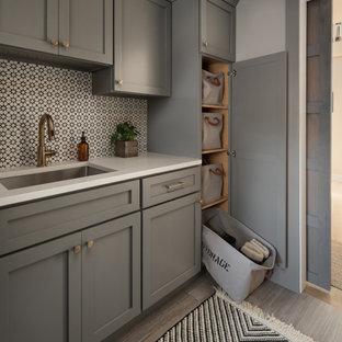 Inredning av ett klassiskt mellanstort vit linjärt vitt grovkök, med en undermonterad diskho, skåp i shakerstil, grå skåp, bänkskiva i kvarts, flerfärgad stänkskydd, stänkskydd i cementkakel, grå väggar, klinkergolv i porslin, en tvättmaskin och torktumlare bredvid varandra och grått golv