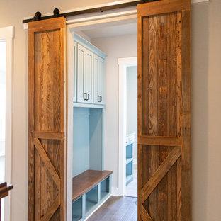 Idéer för att renovera en mellanstor lantlig flerfärgade parallell flerfärgat tvättstuga enbart för tvätt, med en undermonterad diskho, skåp i shakerstil, blå skåp, granitbänkskiva, grå väggar, mellanmörkt trägolv, en tvättmaskin och torktumlare bredvid varandra och brunt golv