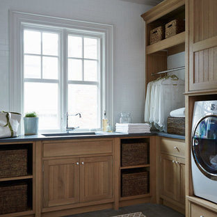 Dedicated laundry room - mid-sized victorian l-shaped gray floor dedicated laundry room idea in Jacksonville with an undermount sink, shaker cabinets, medium tone wood cabinets, white walls and a side-by-side washer/dryer