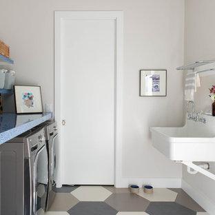 Immagine di una sala lavanderia design con lavatoio, pareti beige, lavatrice e asciugatrice affiancate, pavimento multicolore e top blu
