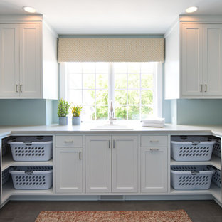 Large transitional u-shaped dedicated laundry room in Minneapolis with a drop-in sink, shaker cabinets, white cabinets, onyx benchtops, blue walls, a side-by-side washer and dryer, grey floor and white benchtop.