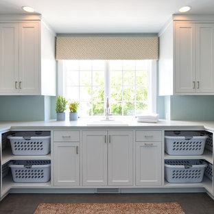 ミネアポリスの大きいトランジショナルスタイルのおしゃれな洗濯室 (ドロップインシンク、シェーカースタイル扉のキャビネット、白いキャビネット、オニキスカウンター、青い壁、左右配置の洗濯機・乾燥機、グレーの床、白いキッチンカウンター) の写真