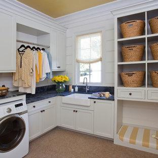 Idéer för att renovera en vintage svarta l-formad svart tvättstuga enbart för tvätt, med en rustik diskho, skåp i shakerstil, vita skåp, en tvättmaskin och torktumlare bredvid varandra och korkgolv