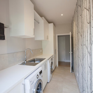 Inspiration for a large nautical galley separated utility room in Auckland with a built-in sink, flat-panel cabinets, white cabinets, porcelain flooring and a side by side washer and dryer.