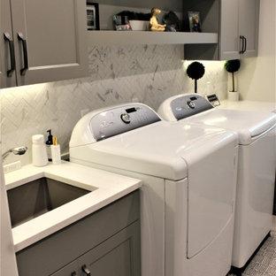 Idéer för att renovera ett stort vintage vit u-format vitt grovkök, med en undermonterad diskho, släta luckor, grå skåp, bänkskiva i kvarts, grått stänkskydd, stänkskydd i stenkakel, grå väggar, klinkergolv i porslin, en tvättmaskin och torktumlare bredvid varandra och grått golv