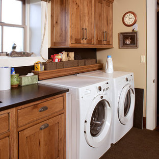 Photo of a medium sized rustic single-wall separated utility room in Miami with a submerged sink, shaker cabinets, dark wood cabinets, granite worktops, beige walls, laminate floors, a side by side washer and dryer, brown floors and black worktops.