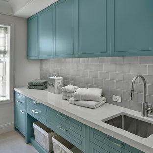 Inredning av en klassisk mellanstor vita parallell vitt tvättstuga enbart för tvätt, med en undermonterad diskho, gröna skåp, bänkskiva i kvarts, grått stänkskydd, stänkskydd i cementkakel, vita väggar, klinkergolv i porslin och beiget golv