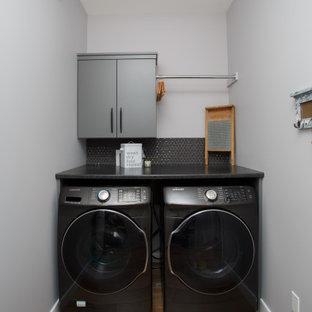 Foto på en liten funkis svarta linjär tvättstuga enbart för tvätt, med släta luckor, grå skåp, laminatbänkskiva, svart stänkskydd, stänkskydd i mosaik, grå väggar, laminatgolv, en tvättmaskin och torktumlare bredvid varandra och blått golv