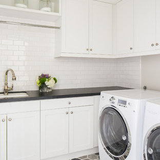 Photo of a classic l-shaped separated utility room in Orange County with a submerged sink, white cabinets, a side by side washer and dryer, multi-coloured floors, black worktops, shaker cabinets and grey walls.