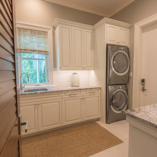 Inspiration for a large tropical galley ceramic floor dedicated laundry room remodel in Tampa with an undermount sink, raised-panel cabinets, white cabinets, granite countertops, a stacked washer/dryer and gray walls
